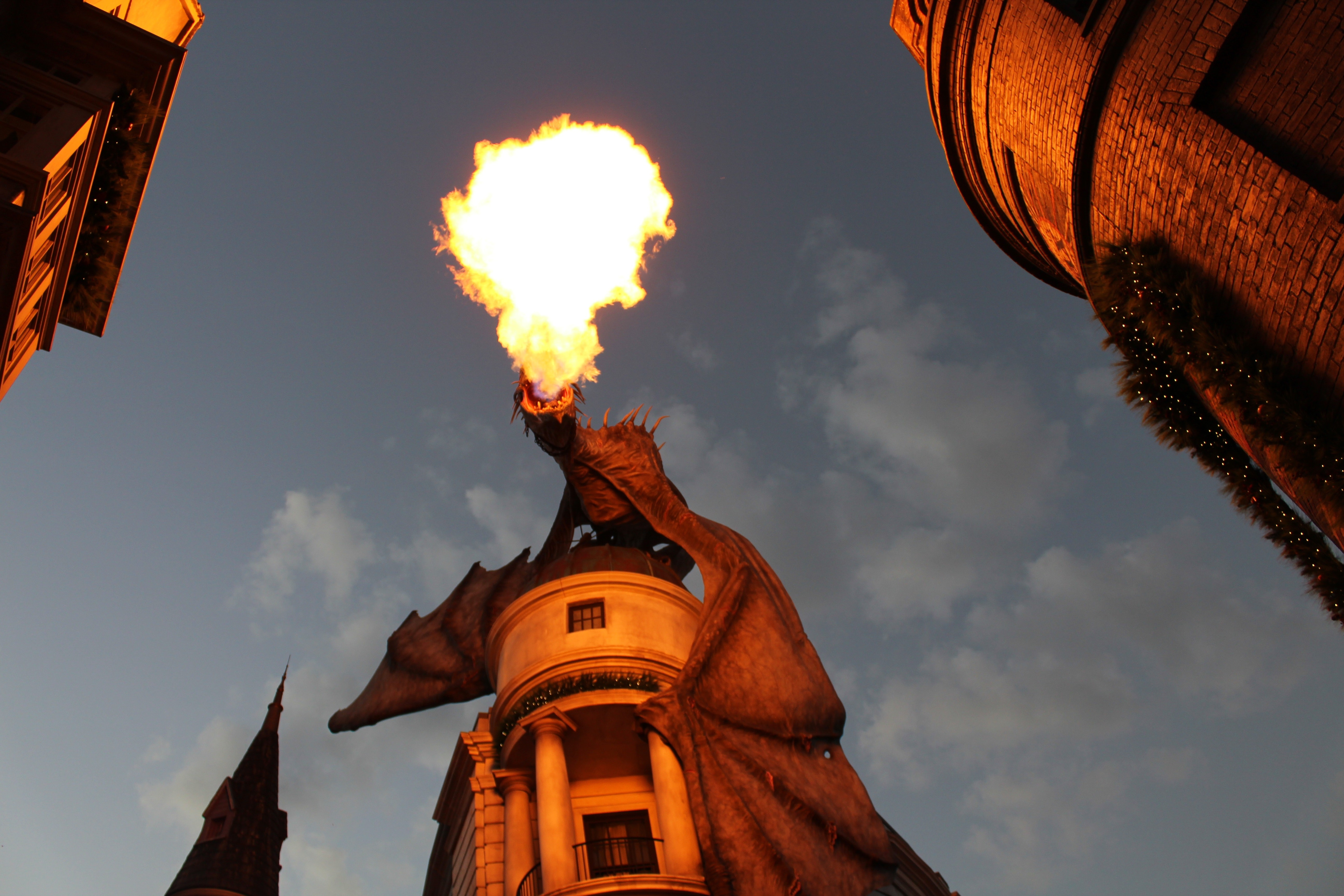 "A fire-breathing ""dragon"" precariously perched atop Gringott's Bank in Universal Studios."